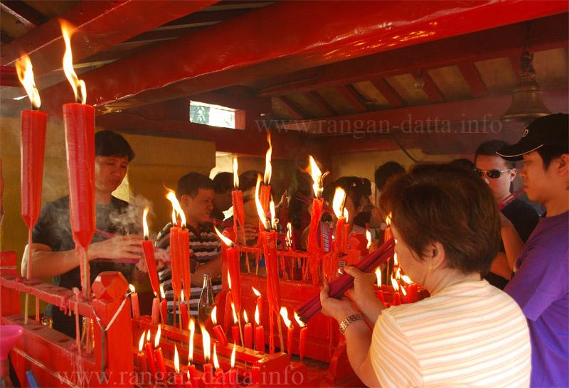 Chinese Devotees light candles, Achipur Chinese Temple. Source ~ rangandatta.wordpress.com