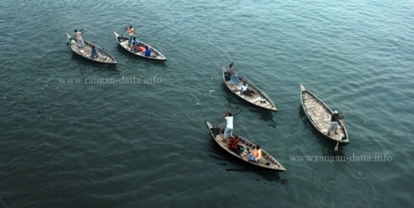 Scattered country boat crossing the Buriganga, Dhaka, Bangladesh