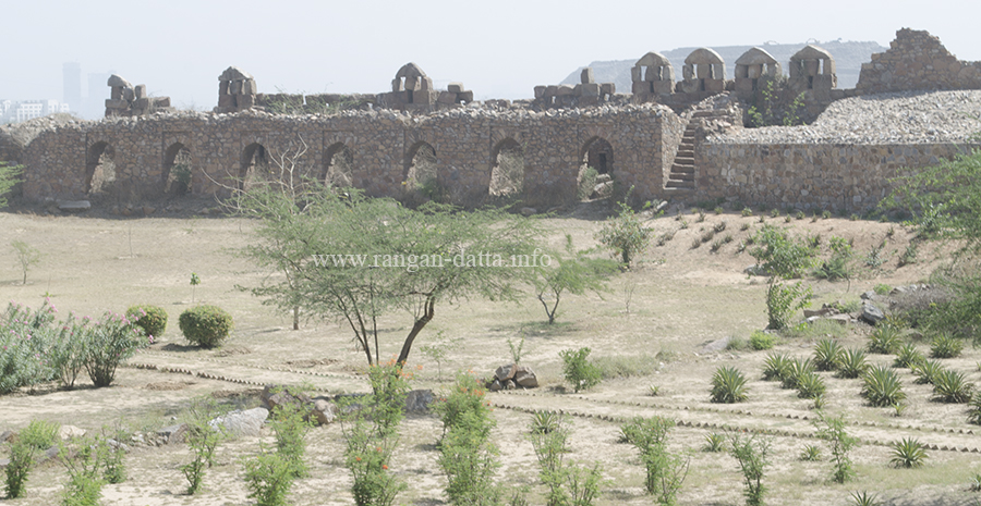 Walls topped with battlements and landscaped gardens inside Adilabad Fort, Delhi