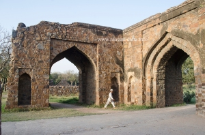 A kid makes his way through the arched gateways of Feroz Shah Kotla, Delhi