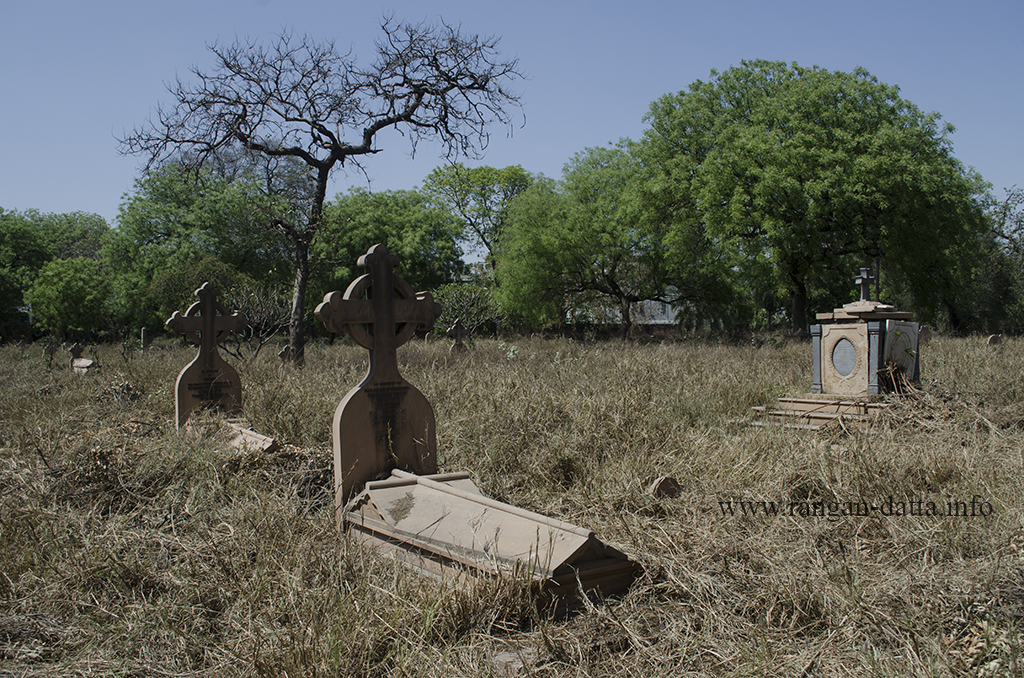 Scattered graves surrounded by over grown grass at Nicholson Cemetery, Kashmir Gate, Delhi