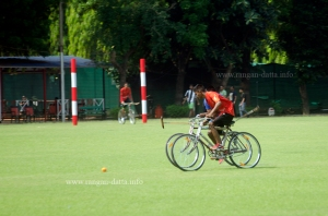 Cycle Polo action with goal post in background