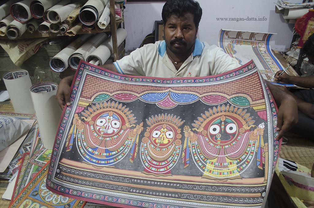 An artist in Raghurajpur displays a patachitra of triad deities of Puri - Jagannath, Balaram and Subhadra, Raghurajpur, Odisha