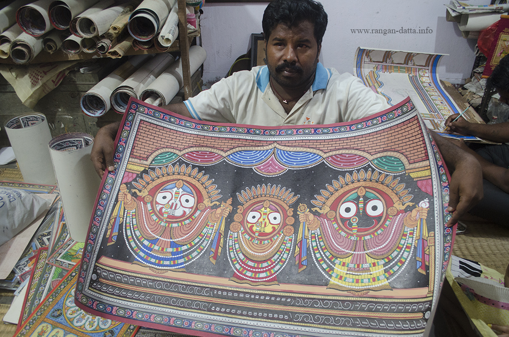 An artist in Raghurajpur displays a patachitra of triad deities of Puri - Jagannath, Balaram and Subhadra, Raghurajpur, Odisha