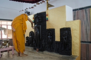 A Jain devotee uses milk and ghee to polish the statues