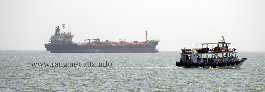 A ferry sails past a gigantic ship, en route Elephanta Island